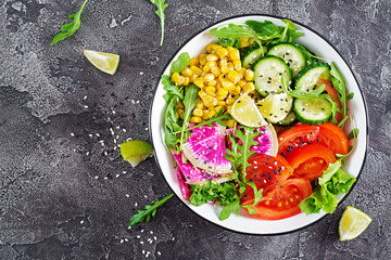 Foto op Aluminium Klaar gerecht Vegan buddha bowl. Bowl with fresh raw vegetables - cucumber, tomato, watermelon radish, lettuce, arugula and corn. Fresh salad. Vegetarian food. Top view. Flat lay