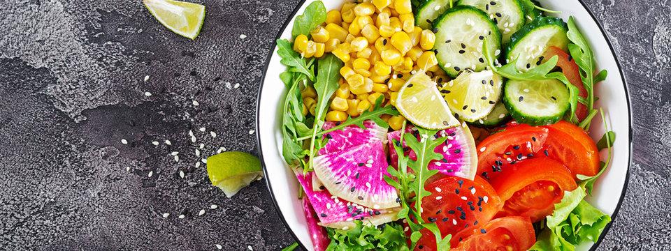 Vegan buddha bowl. Bowl with fresh raw vegetables - cucumber, tomato, watermelon radish, lettuce, arugula and corn. Fresh salad. Vegetarian food. Banner. Top view. Flat lay