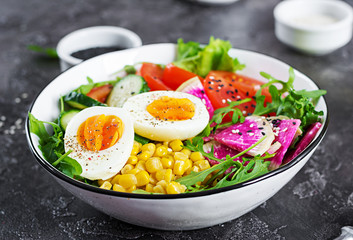 Fresh salad. Bowl with fresh raw vegetables - cucumber, tomato, watermelon radish, lettuce, arugula, corn and boiled egg. Healthy food. Vegetarian buddha bowl.