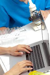 Scientist hands on laptop in lab