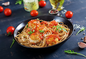 Italian pasta. Spaghetti with meatballs and parmesan cheese in black plate on dark rustic wood background.  Dinner. Slow food concept