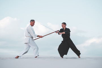 Two men practicing Japanese martial arts in desert