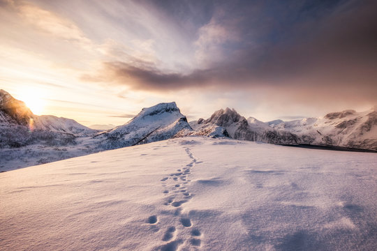 Landscape of snow mountains range with footprint on snowy at sunrise