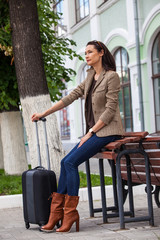 pretty adult woman with a suitcase waiting for a train