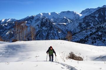 Traveler in the mountains walk on snowshoes. Winter mountain tourism. Kazakhstan