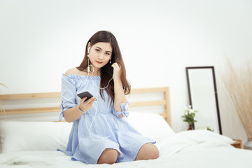 A beautiful Asian woman with headphone relaxing at home , sitting on the bed listening to music from application on mobile phone