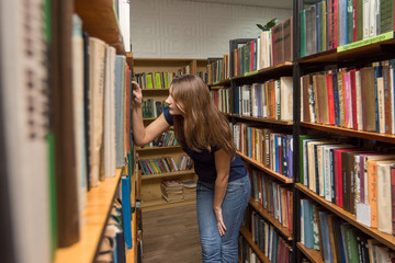 A girl is looking for a book in the library