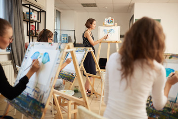 Young girls  and  drawing teacher paint pictures sitting at the easels in the art studio