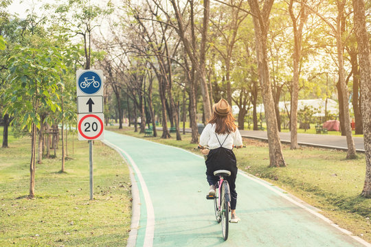 Young woman riding bicycle on bike lane in the park