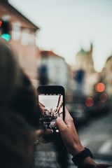 Photo hands with smartphone taken pictures of Prague skyline and buildings