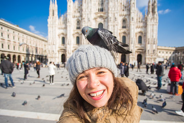 Italy, excursion and travel concept - young funny woman taking selfie with pigeons in front of cathedral Duomo in Milan