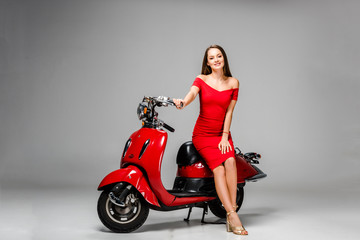beautiful girl in red dress looking at camera and posing while sitting on motor scooter on grey background
