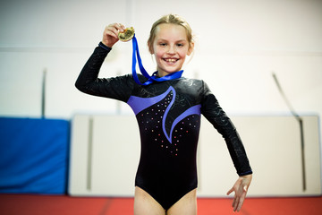 Young gymnast showing her golden medal