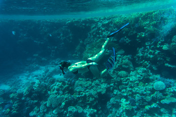 Young woman snorkeling over coral reefs in a tropical sea