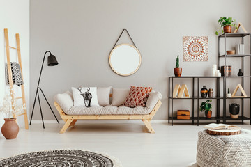 Light grey living room interior with mirror on the wall, couch with cushions and metal rack with decor and fresh plants in real photo