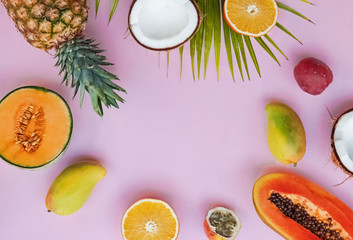 Creative frame with tropic fruits on the pink background