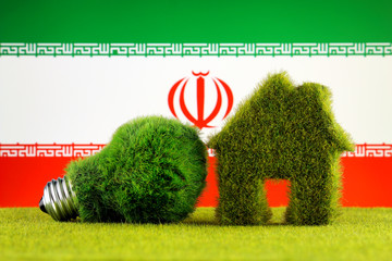 Green eco light bulb, eco house icon and Iran Flag. Renewable energy. Electricity prices, energy saving in the household.