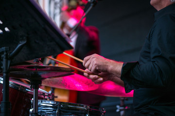Shot of a man playing drums on stage during music festival in summer. Band performing their jazz songs. Live concert of electronic music at night. Male musicians playing saxophone, drums, cello