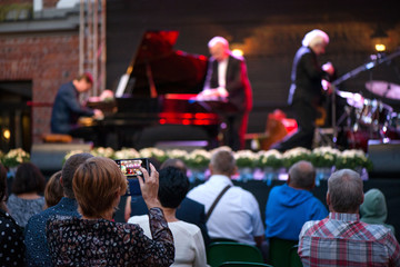 Woman is taking pictures or recording video of jazz concert. Male musicians on stage singing, playing piano, saxophone, drums, cello. Crowded venue. Audience enjoying romantic and relaxing evening
