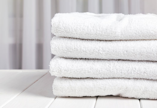 Stack of the cotton white tovels on the white wooden table