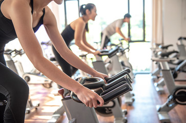 Select focus of hand Attractive woman  biking in gym, exercising legs doing cardio workout cycling bikes - Image
