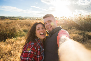 Travel, holidays and nature concept - Happy couple taking a selfie at a field
