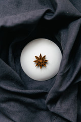 Star anise on a white bowl surrounded by dark grey fabric.