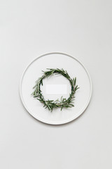 A small rosemary wreath on a decorated tabletop with a white plate.