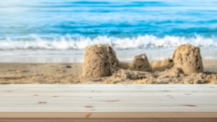 Empty table top for product display montage. Family holiday concept. Sand castle on beach blurred in the background.
