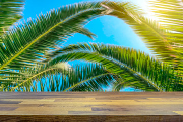 Empty table top for product display montage. Tropical holiday concept. Palm tree and beautiful blue sky blurred in the background.