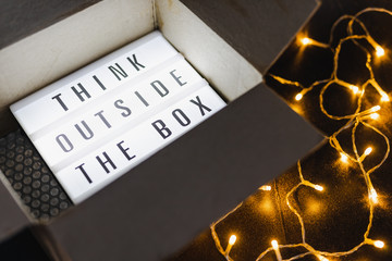 Think outside the box message on lightbox coming out of a parcel with fairy led lights