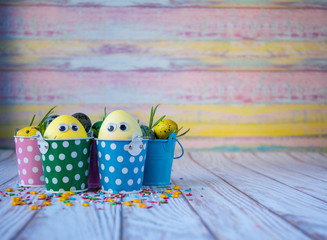 Easter background. Funny easter eggs painted yellow on color background. Easter holiday concept. Copy space, horizontal