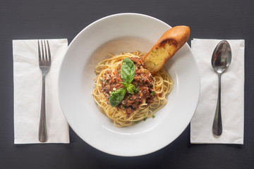 Pasta bolognese on a white plate on a dark background