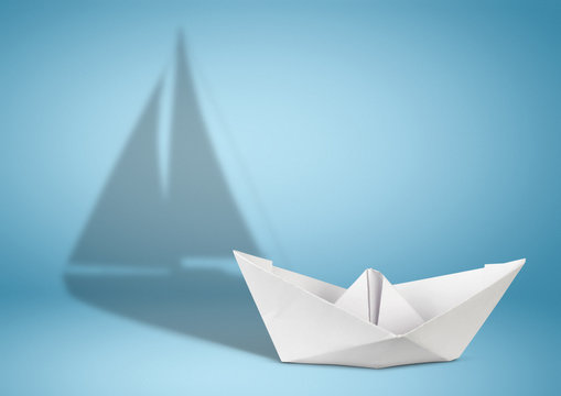 Sailing yacht concept, paper ship with sailing boat shadow