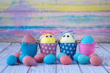 Easter background. Funny easter eggs painted yellow on color background. Easter holiday concept. Copy space, horizontal.