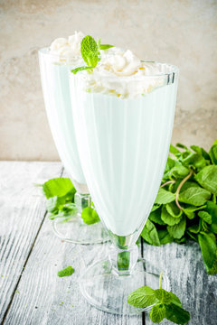 Summer refreshing cocktail, shamrock mint shake, sweet milk drink with fresh mint leaves, wooden background copy space