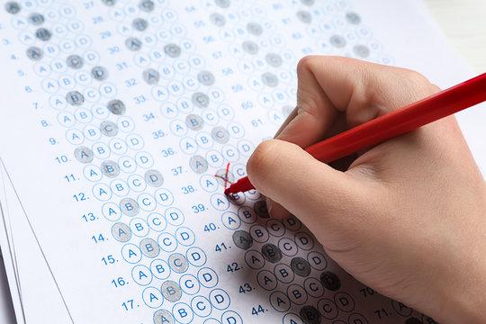 Teacher checking answer sheet after exam, closeup