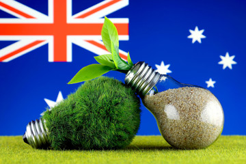 Green eco light bulb with grass, plant growing inside the light bulb, and Australia Flag. Renewable energy. Electricity prices, energy saving in the household.