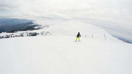 A girl rides a snowboard in the mountains. Lots of snow. Carpathians. Ski jacket and trousers.