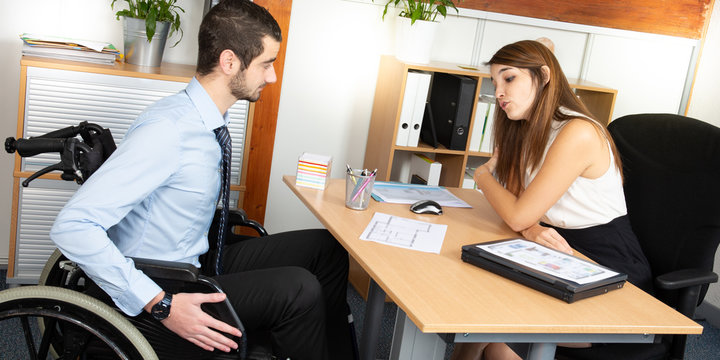 man Sitting In Wheelchair Working In Modern Office having discussion with female colleague