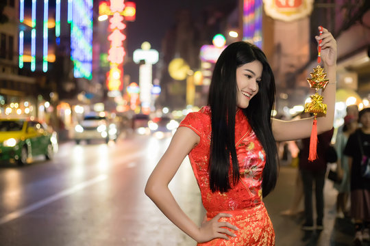A beautiful, long-haired Thai woman, an Asian woman wearing a Chinese dress, standing smiling and Holding a Chinese tassel at Roadside Chinatown, Yaowarat, Bangkok, Thailand at night.