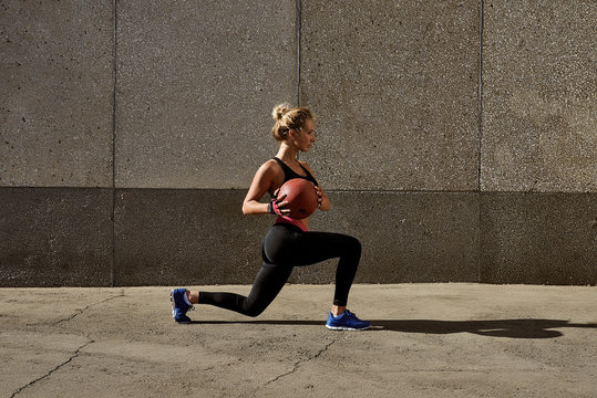 Fitness woman working out at outdoors gym using medicine ball. Sportswoman stretching outdoors with medicine ball. Copyspace for text
