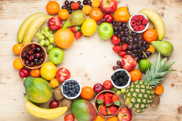 Rainbow fruits background circle frame, strawberries raspberries oranges plums apples kiwis grapes blueberries mango persimmon on light wooden table, top view, copy space for text, selective focus