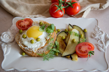 Dried egg on toast bread, eggplant, tomatoes and green peas as breakfast on white plate