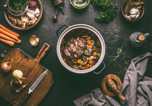 Cooking preparation of stewed meat.  Roasted beef meat in cast iron cooking pot with vegetables on dark rustic background with kitchen utensils and seasoning, top view with copy space.