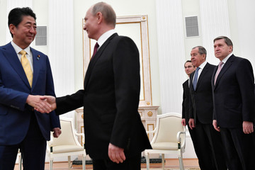 Russian Foreign Minister Lavrov and presidential aide Ushakov watch Russian President Putin shaking hands with Japanese Prime Minister Abe during a meeting in Moscow
