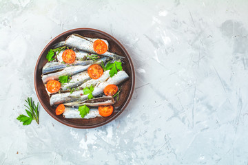 Sardines or baltic herring with rosemary, parsley, tomatoes slices and spaces on ceramic plate