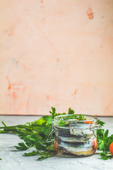 Preserved marinated sea fish in glass jar on gray concrete table