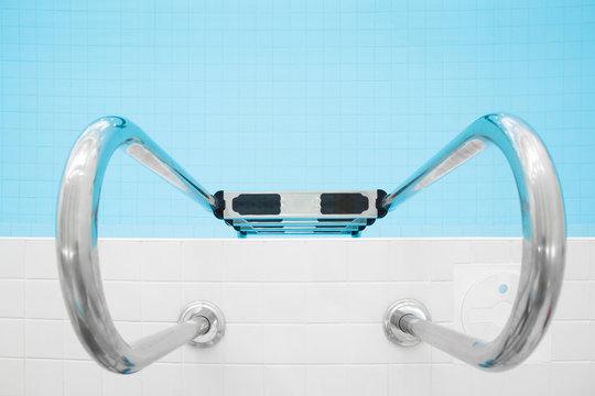 Metallic ladder in swimming pool. Closeup.