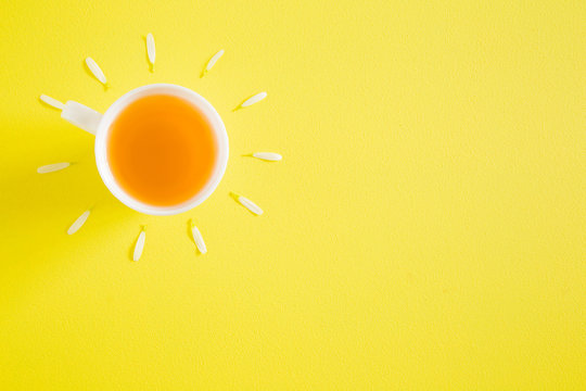 White cup of herbal tea on bright yellow table. Wake up with hot drink. Sun rays created from chamomile petal. Empty place for inspirational, motivational, positive text, quote or sayings. Top view.